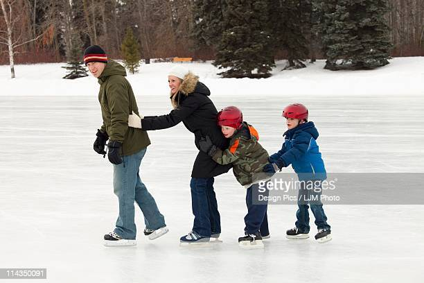 A Family Skating Together On An Outdoor Ice Rink