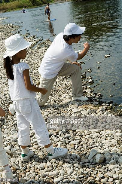 Family skipping stones by river