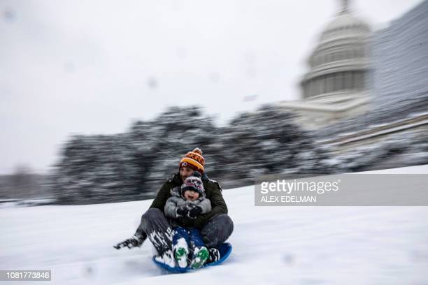 TOPSHOT A family sleds down the West Front of the US Capitol as snow continues to fall in Washington DC on January 13 2019 Washington area residents...