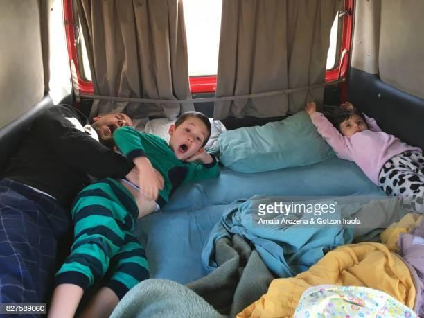 family sleeping inside a camper van - wohngebäude innenansicht stock-fotos und bilder