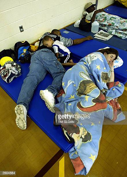 A family sleeps on gym mats 17 September at the Birdneck Elementary School gym which already has over 70 Virgina Beach Virginia residents seeking...