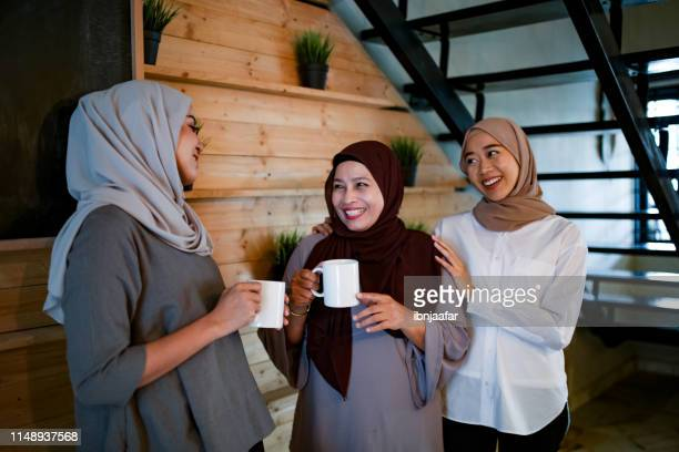 family smiling and talking to each other - eid al adha stock pictures, royalty-free photos & images
