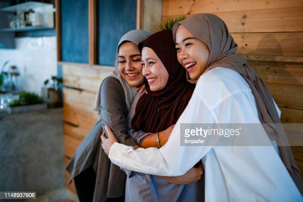 family smiling and talking to each other - hari raya celebration stock pictures, royalty-free photos & images