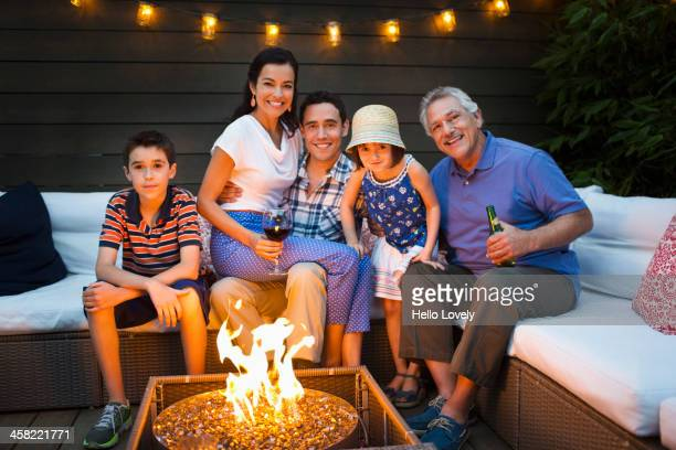 Family smiling around fire pit outdoors