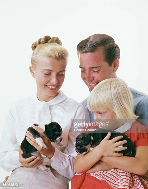 family smiling holding newborn puppies - mamífero con garras fotografías e imágenes de stock