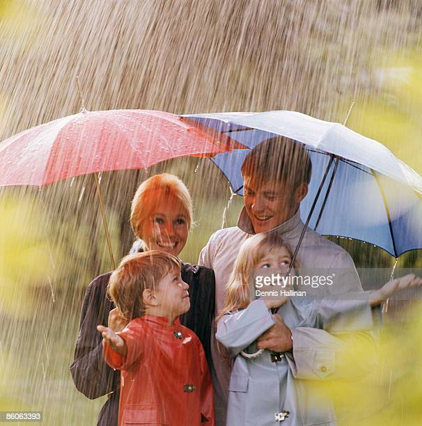 family smiling holding umbrellas standing in the rain - vintage raincoat stock photos and pictures