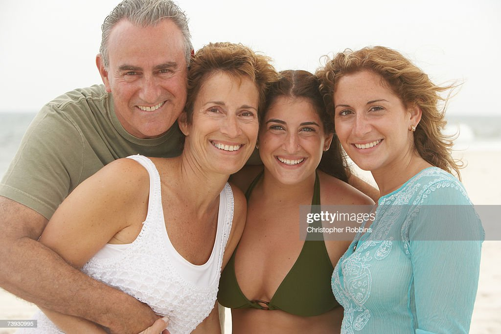 Family smiling on beach, waist up : Stock Photo