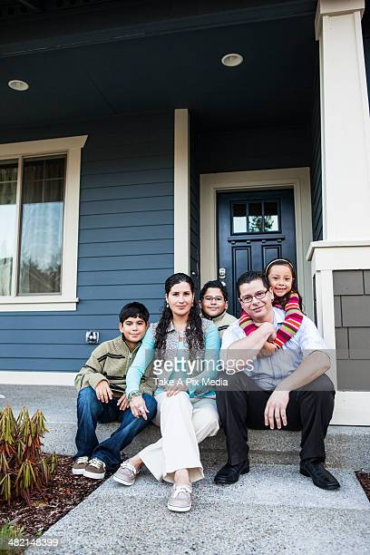 Family smiling on front stoop