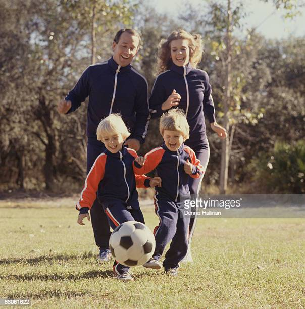 Family smiling playing soccer wearing track suits