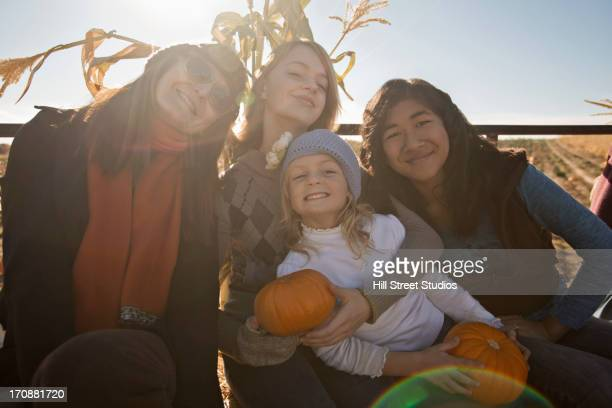 Family smiling together in pumpkin patch