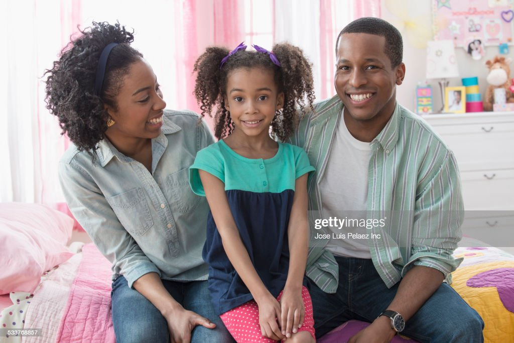 Family smiling together on bed : Foto stock