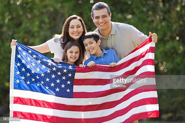 Family Smiling While Holding American Flag At Park