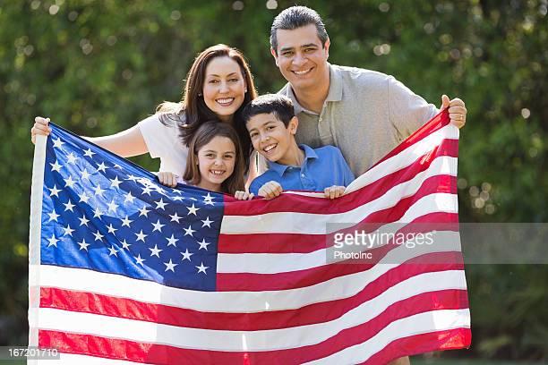 Família sorridente segurando bandeira americana no parque