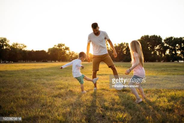 family soccer game - public park stock photos and pictures