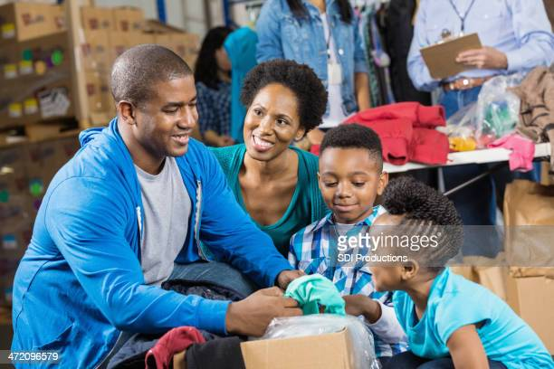 Family sorting clothing donations together at charity drive
