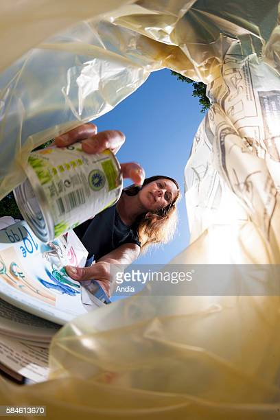 woman throwing a recyclable can into a yellow trash bag