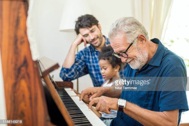 family spend time happy together. grandfather playing piano with his granddaughter and son together in living room at home. - life insurance stock pictures, royalty-free photos & images