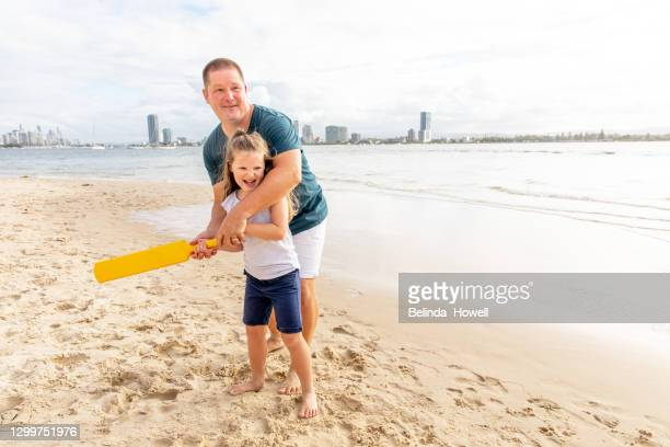 family spends time at the beach playing together on the sand - cricket stock pictures, royalty-free photos & images