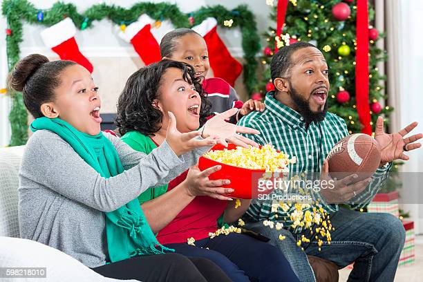 Family spills popcorn while watching excited football game