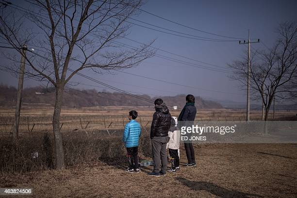 A family stand facing in the direction of North Korea at Imjingak park south of the Military Demarcation Line and Demilitarized Zone separating North...
