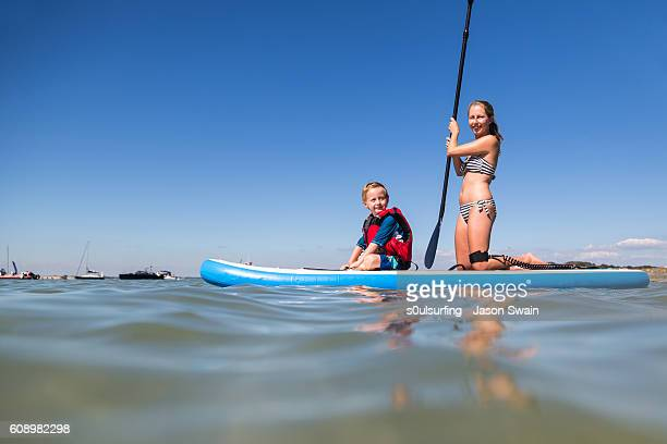 family stand up paddleboarding on the isle of wight. - s0ulsurfing stock pictures, royalty-free photos & images