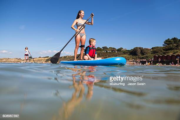 family stand up paddleboarding on the isle of wight. - isle of wight stock photos and pictures