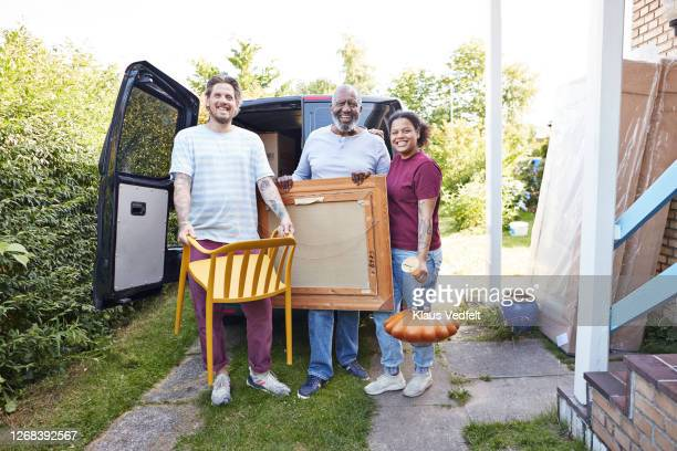family standing against van outside new house - african american man helping elderly stock pictures, royalty-free photos & images