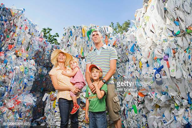 family standing amongst recycled materials, smiling - omgeven stockfoto's en -beelden