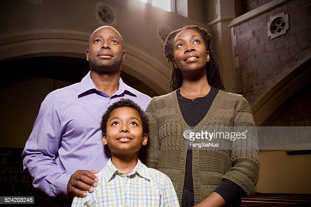 family standing and praying in church - the god father stock photos and pictures
