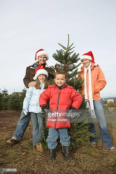 Family standing around Christmas tree