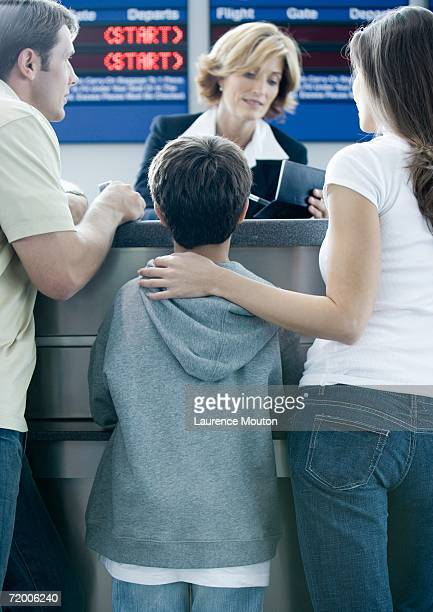 Family standing at airline check-in counter