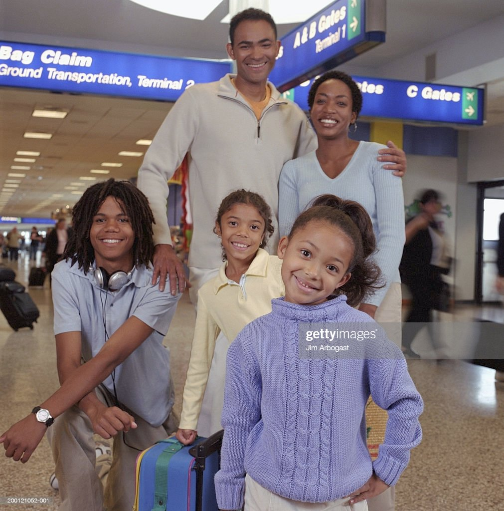 Family standing at baggage claim in airport, portrait : Stock Photo