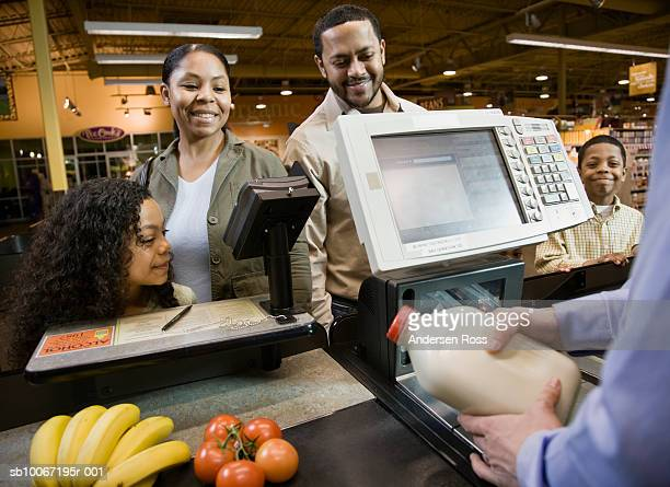 Family standing at checkout, smiling