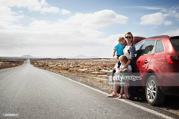 Family standing by broken down car