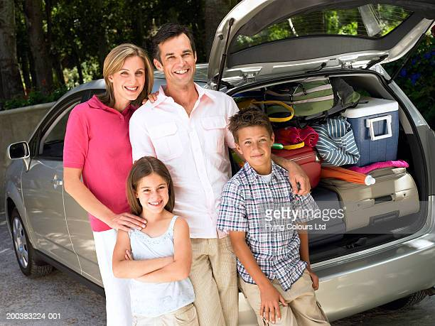 Family standing by car loaded with cases, smiling, portrait