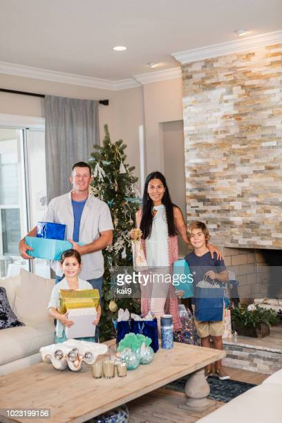 family standing by christmas tree holding gifts - southern christmas stock pictures, royalty-free photos & images