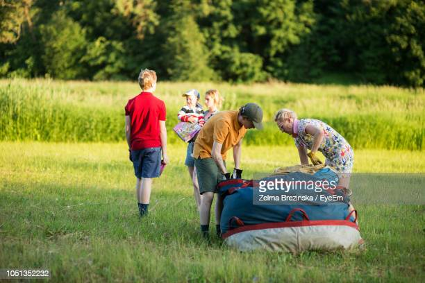 Family Standing By Pilot And Boy Preparing Hot Air Balloon On Grassy Field During Sunset