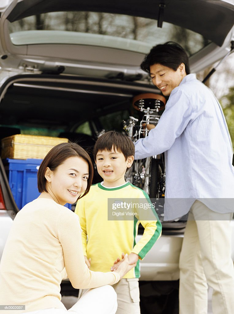 Family Standing by the Back of Car, with the Father Removing a Bicycle : Stock Photo