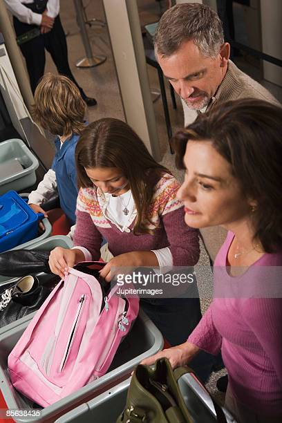family standing in airport security checkpoint - security check stock photos and pictures