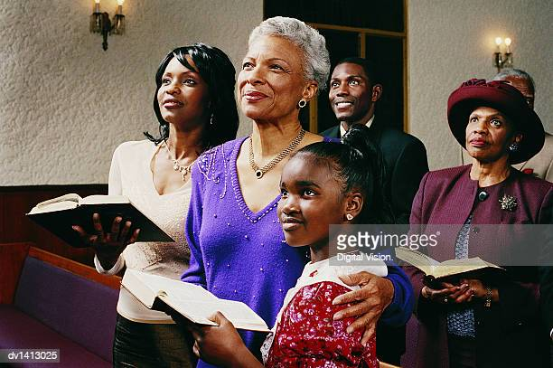 family standing in church pews holding bibles and listening to a service - congregation stock pictures, royalty-free photos & images