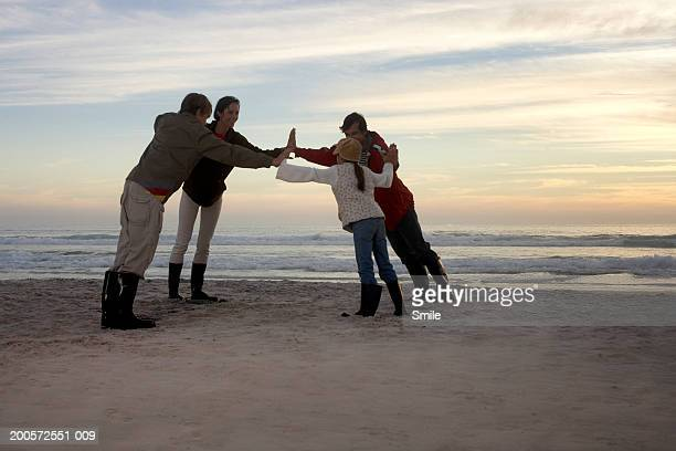 Family standing in circle on beach