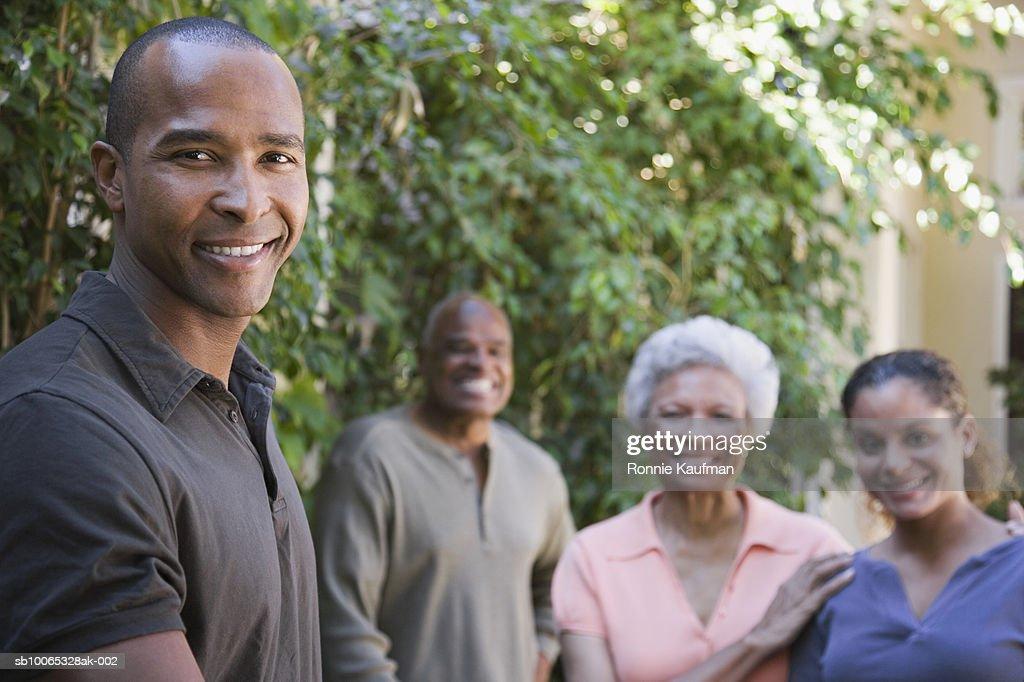 Family standing in domestic garden, smiling : Foto stock
