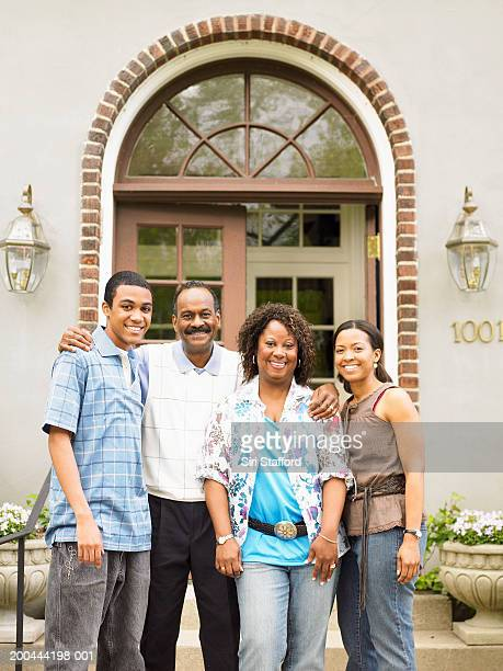 Family standing in front of home, portrait