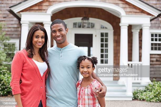 Family standing in front of residential home