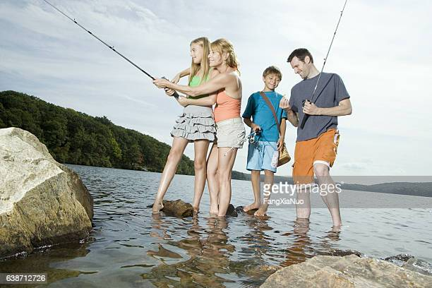 family standing in lake fishing together - the god father stock photos and pictures