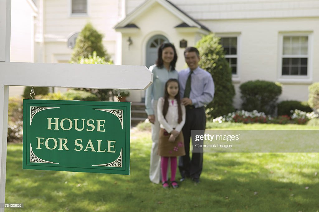Family standing in lawn with real estate sign : Stockfoto