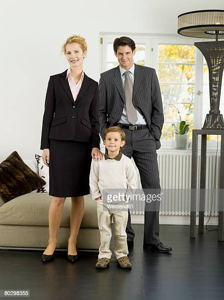 Businessman and woman standing with son (3-4), smiling, portrait