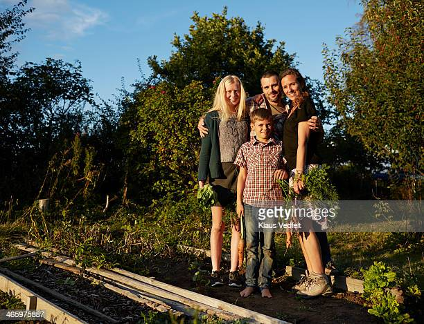 Family standing in their vegetable garden