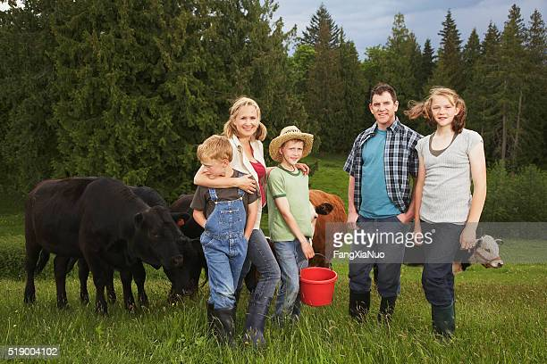 Family standing near cattle on farm