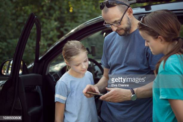 family standing next to a car and using a portable information device - portable information device imagens e fotografias de stock